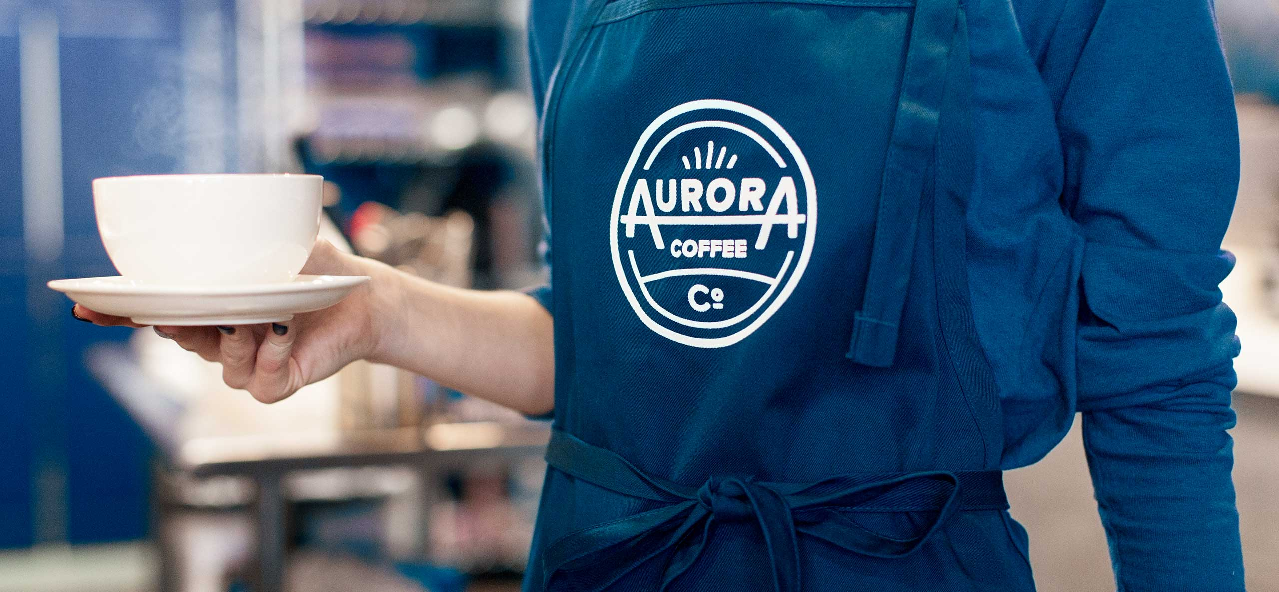 Aurora Barista holding coffee mug in apron